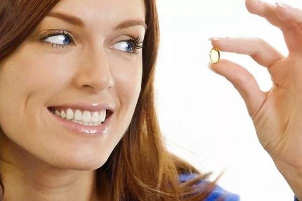 Девушка держит капсулу Омега-3