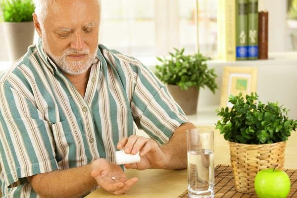 Мужчина принимает лекарство от гиперхолестеринемии